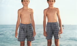 A color photograph of two light-skinned young boys in plaid swimsuits standing side-by-side at the edge of the water on a rocky beach.