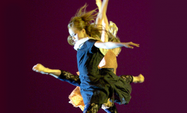 two dancers mid jump with one leg and both arms raised