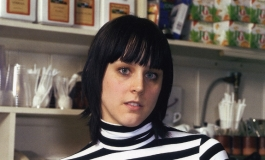 A color photograph of a young woman with light skin and dark hair in a black-and-white striped turtleneck standing behind a cafe counter.