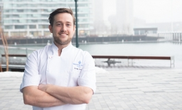 Chef Charlie Foster, in his chef's uniform, arms crossed and smiling, with Boston Harbor in the background.