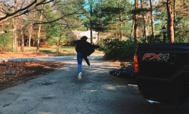 A young person jumping mid-air over an asphalt driveway in a rural neighborhood.
