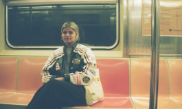 A medium dark skinned person with blonde hair riding on a subway train.