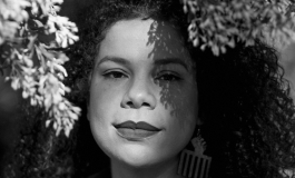 A black-and-white portrait of artist Firelei Báez, a light skinned Latinx woman with curly hair standing underneath a tree.