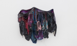 A sculpture mounted on the wall and composed of a cluster of colorful housedresses.