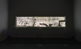 "An installation shows a projection of a map with text that reads ""bring enemy revolverr,"" ""I assure you, we are not afraid. We are not sentimental,"" ""annihilate,"" and ""brutes"" in all caps and in various parts of the map."
