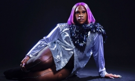 A person in a purple wig, black feather boa, shiny jacket, and ripped fishnets lounges on one hip on a dark stage.