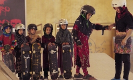 A group of girls wearing helmets and headscarves standing in a line holding skateboards.