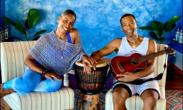 Two people, a wife and husband, sitting in a tropical interior room with their hands touching over a djembe drum and the husband holding a guitar.