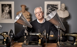 A portrait of artist William Kentridge, an elderly white man, standing behind a table with antique sewing machines and silver megaphones attached to them; behind him are classical bust sculptures and prints.