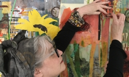 Artist Merill Comeau sewing fabric onto a large mural resembling a floral landscape.