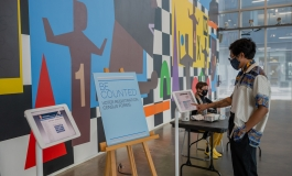 "In front of ICA's art wall, a medium dark-skinned man points to an iPad device on a stand and a sign that reads ""Be Counted"" sits on an easel display."