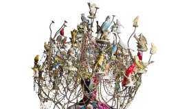 A sculpture composed of a colorful costume covering the body of a mannequin a chandelier-like headpiece decorated with ceramic birds and strings of beads.