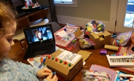 A young child creating an art piece on a dining table with their laptop open and various art supplies.