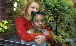 A light-skinned young woman with curly blond hair and a red sweater hugs a dark-skinned child with high braided pigtails behind a window. Both look at the camera. Tree leaves are reflected in the glass, and on the left side.