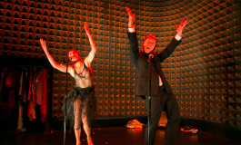 two people in black costumse lit by a red light with their hands in the air singing into microphones