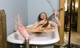 A video still shows the artist, a white man, in a bathtub, wearing headphones, and plays the guitar, and apparently nude.