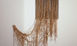 An installation of ochre- colored string attached in a regular pattern to a piece of grey painted plywood but tangling as they fall to the floor or are attached loosely to the adjacent wall.