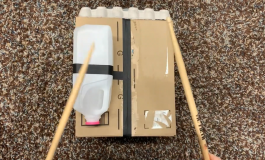 An aerial image of a pair of hands holding sticks while striking a DIY drum made of a box, a milk carton, and an egg carton.