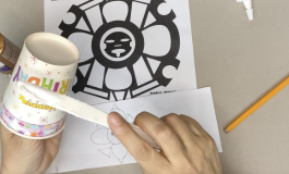 A pair of hands applying glue to a paper cup with a plastic knife. A flower drawing and design on the table.