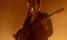 A sepia-toned image of Tamino playing guitar and singing into a microphone.