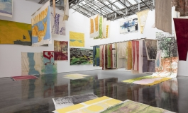 A photograph shows a room full of colorful unframed canvases hung from walls and the ceiling at different angles.