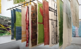 Unframed canvases painted with abstract shapes hang from a metal rack suspended from the ceiling in a gallery space.